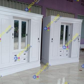 lemari pakaian modern dengan desain minimalis atau yang biasa disebut dengan almari modern cat duco putih pintu geser bahan kayu jati